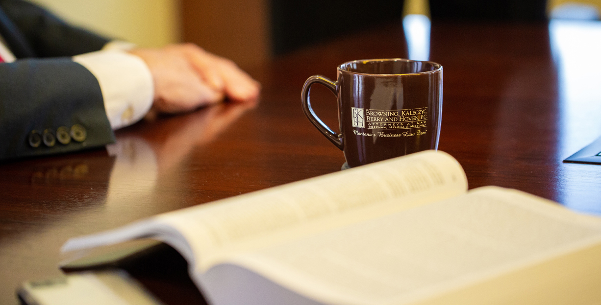 Open book, coffee cup, and hand on desk.