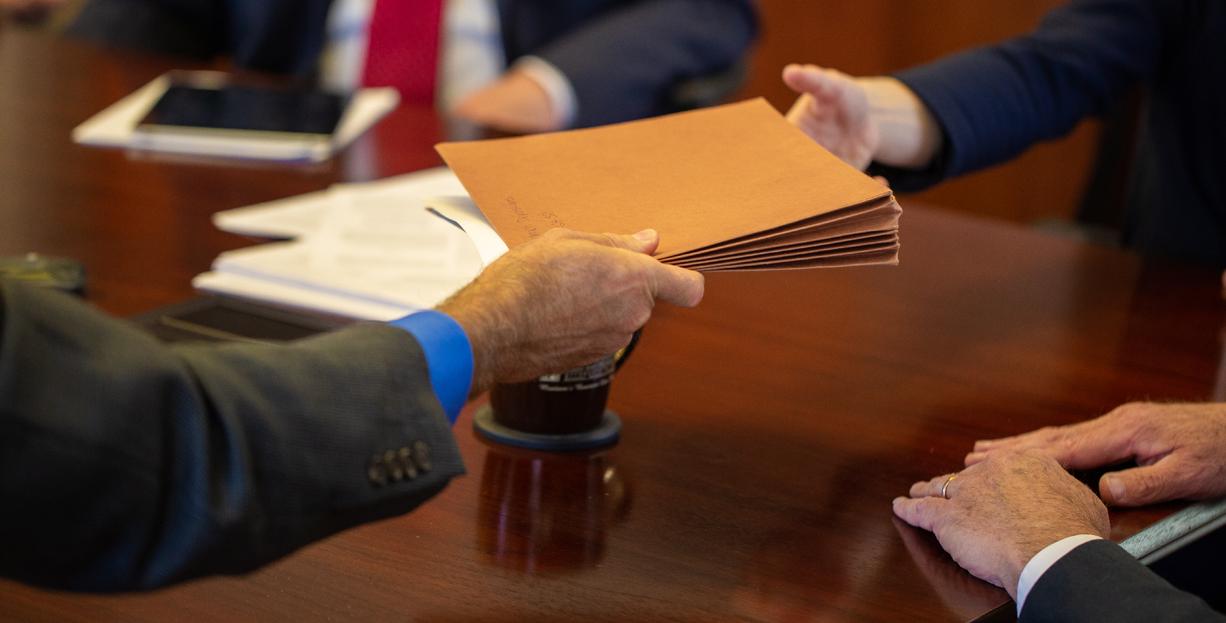 Handing folder across table
